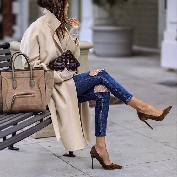 Sasha Simon wears a striking pair of suede stilettos with distressed blue denim jeans and a cream coloured overcoat. This style is completed with a large hangbag and mini YSL clutch. Brands not specified.