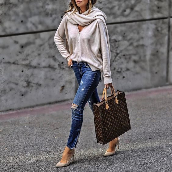 Sasha Simon pairs a blissfully soft cashmere cardigan with distressed denim jeans, cream suede heels, and a striking Vuitton bag. This look is perfect for everyday wear. Cardigan: Softgoatcashmere.