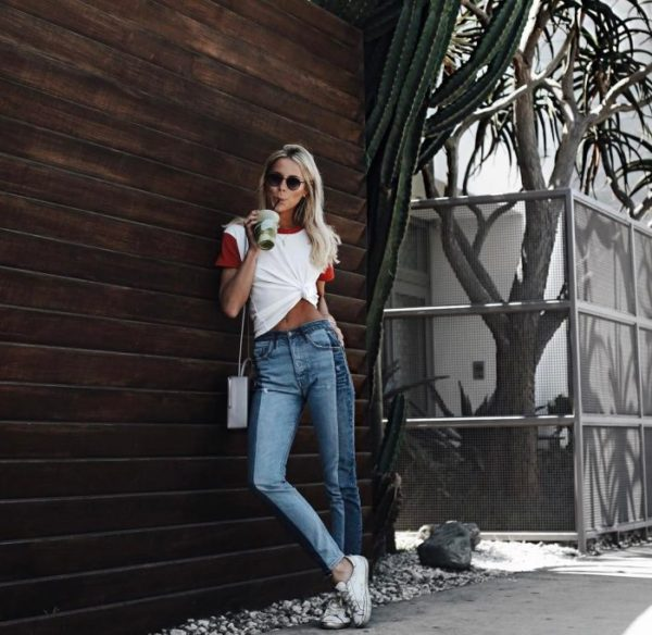 Mary Seng wears a tie-front baseball style tee, with red sleeve and collar detailing. Pairing this tee with two-tone denim jeans and white sneakers, Mary has created a great spring style. Brands not specified.