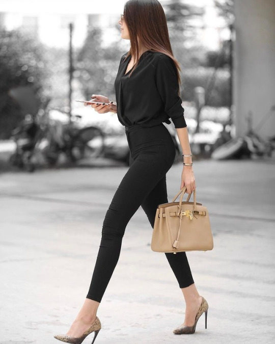 Merve Aydogdu rocks a classic style here, in a predominantly black spring outfit consisting of a V neck top, high waisted jeans, and a pair of faux snakeskin heels. Brands not specified.