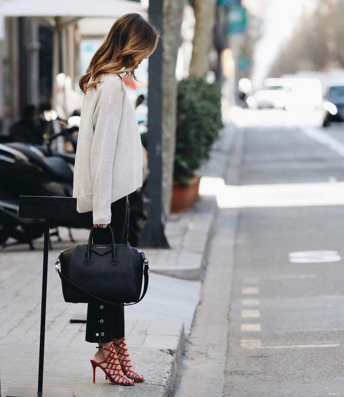 Alex Riviere is rocking a super glam spring look, wearing a loose fitting cream sweater, with button down cigarette trousers and a pair of striking scarlet stilettos. Brands not specified.