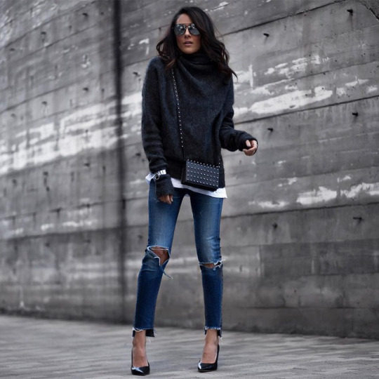 Lucy Hernandez pairs distressed denim jeans with patent navy stilettos and an oversized dark grey turtleneck to form this cosy and comfortable spring outfit. Brands not specified.