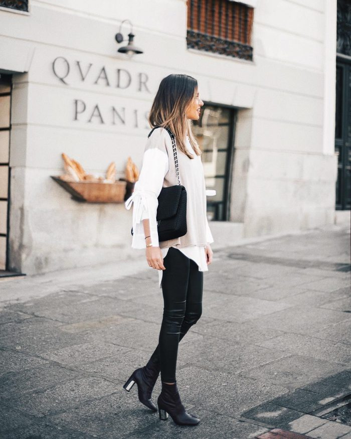 Alba Hervas wears tight leather leggings with sleek black boots, a layered white blouse with cutaway sleeves, and a beige top. Alba pairs this look with a lush black handbag. Brands not specified.
