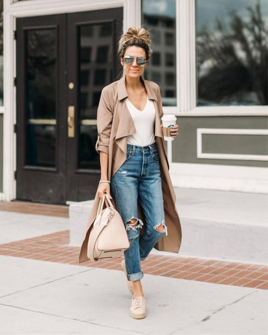 Christine Andrew wears a pair of ripped denim jeans, rolled at the ankle, paired with a white V neck tee and a blush pink coat and sneakers. These neutral, calming tones are perfect for spring mornings. Brands not specified.