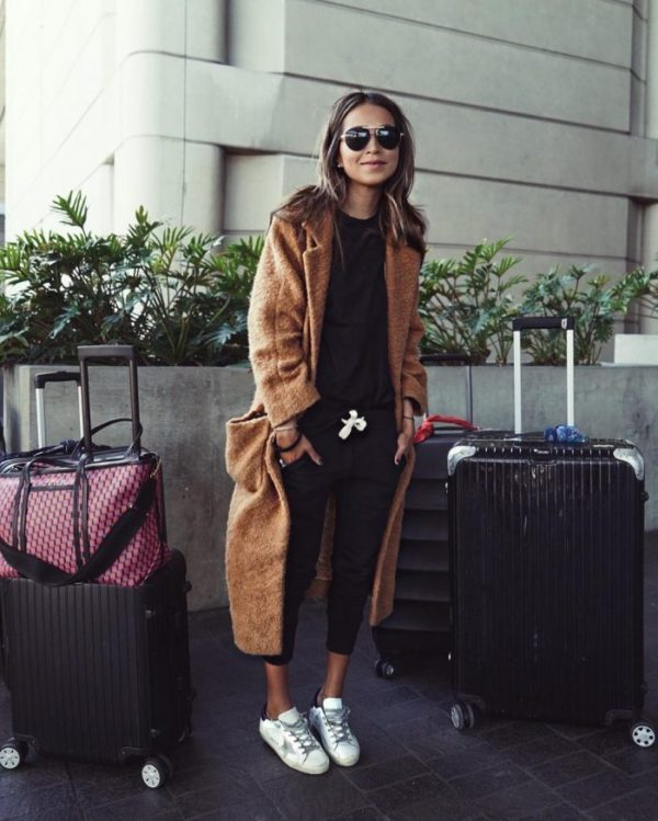 Julie Sarinana is wearing a pair of cropped black tracksuit pants with a matching black tee, white sneakers, and a long brown maxi coat. We like the comfort factor of this look. Coat: Ganni.