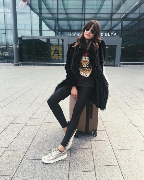 Michelle's travel style consists of leather leggings, a classic Ramones band tee, and an oversized faux fur coat. Michelle wears this style with metallic sneakers for an edgy but effective travel outfit. Coat: Gorski Outerwear, Trainers: Tretorn.
