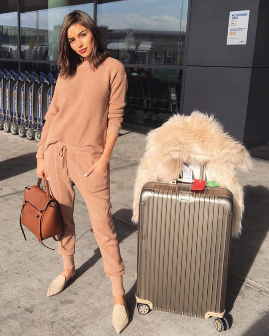 Olivia Culpo wears head to toe beige here, creating a comfortable yet sleek travel style which is perfect for any journey! Olivia wears this look with suede flats, and carries a gorgeous faux fur cream coat. Top: Thakoon, Shoes: Nicholas Thirkwood.