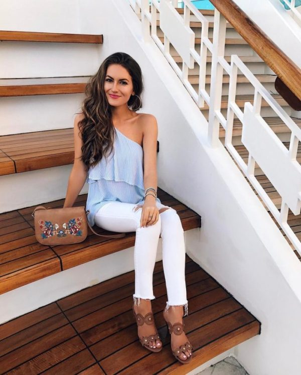 Caitlin knows that blue pinstripes go a treat with white jeans, as she pairs the two in an off the shoulder tank top, and distressed jeans. Finish this style with statement heels to complete the look. Shoes: Jack Roger.
